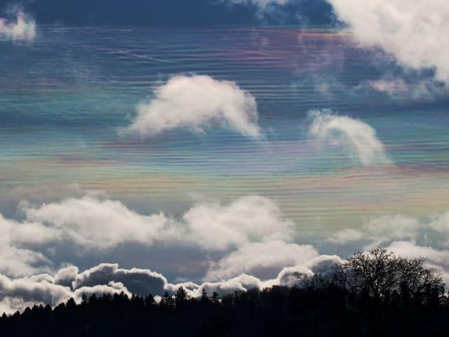 In Richtung Süden zeigen sich Irisierende Wolken. Die streifenartigen dünnen hohen Wolkenfelder weisen Regenbogenfarben auf. Im Vordergrund hat es weisse kleine Quellwolken.