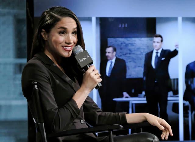 Frau sitzend mit Mikrofon in der Hand.