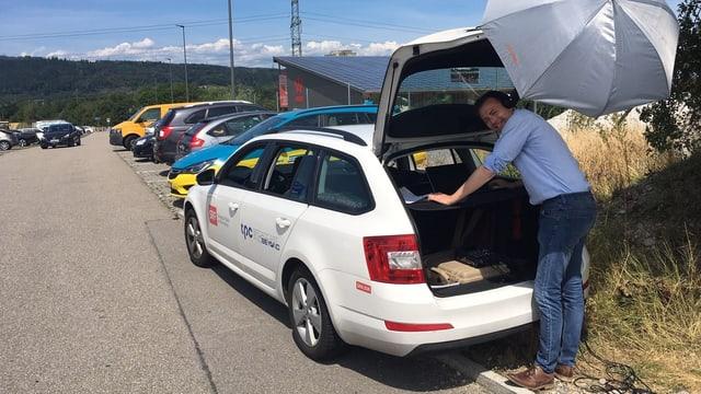 Mann steht bei offenem Kofferraum von Auto.