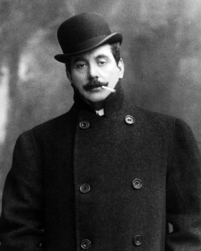Puccini mit Mantel, Hut und Zigarette.