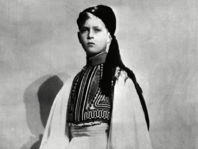 Schwarz-weiss-Aufnahme von Prinz Philip als Kind. Er trägt eine griechische Tracht.