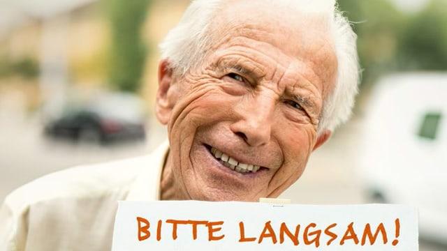 Ein freundlich lächelnder Senior hält ein Schild hoch mit der Aufschrift: «Bitte langsam, ich bin es auch».