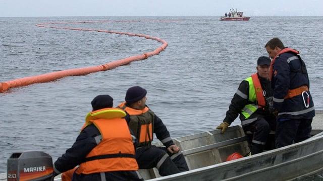 Männer auf einem Boot kontrollieren eine schwimmende Absperrung um eine Verschmutzung im Genfersee.