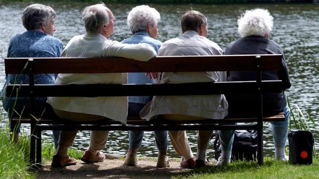 Fünf Rentner sitzen auf einer Bank, man sieht alle von hinten.