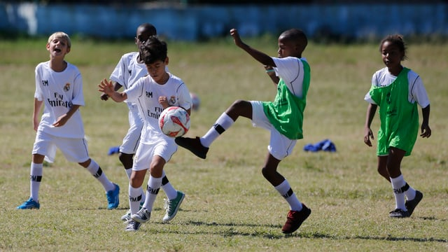 Kinder in Shirts von Real Madrid spielen Fussball.