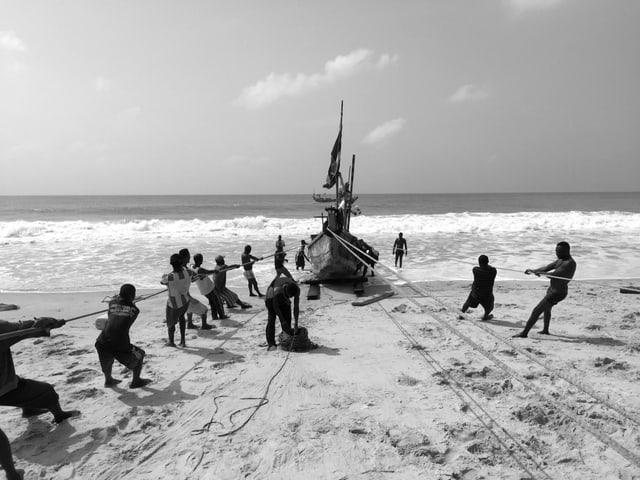 Schwarz-Weiss-Aufnahme: Rund ein Dutzend Männer ziehen das Boot an rund sieben langen Seilen durch den Sand.