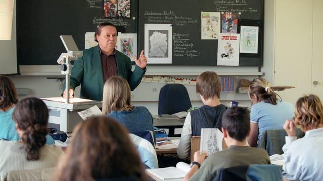 Ein Lehrer steht vor einer Oberstufenklasse und erklärt etwas vor der Wandtafel.