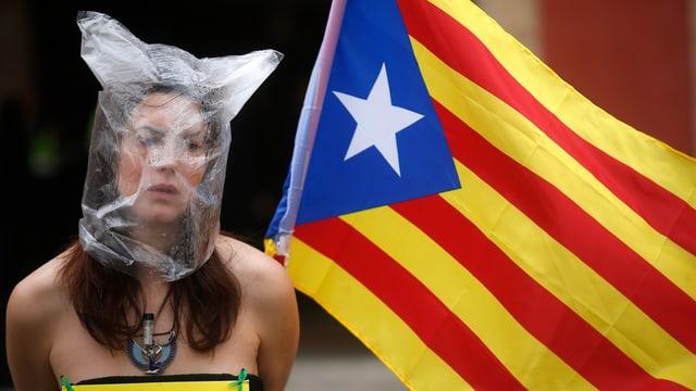 Frau mit Plastiksack auf dem Kopf und nackten Schultern, daneben eine katalonische Flagge.