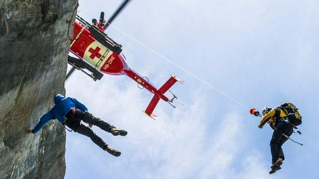Ein Rega-Helikopter rettet einen Kletterer aus einer Felswand.