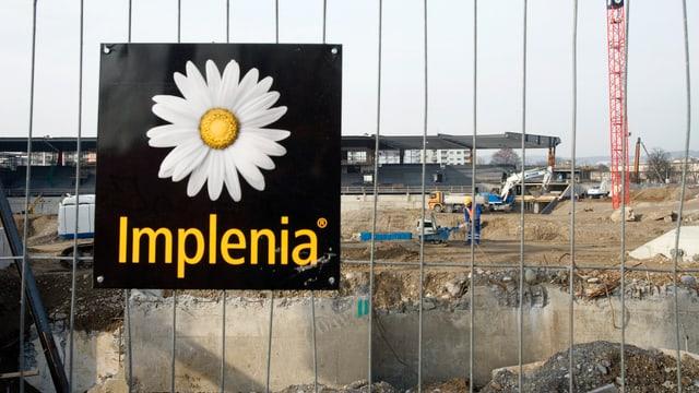 Implenia Logo vor Baustelle