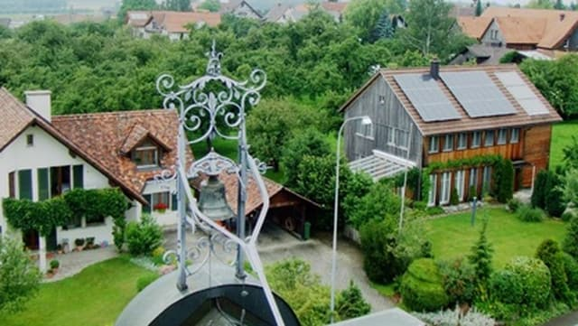 Zwei Häuser, wovon eines Solaranlagen auf dem Dach hat.
