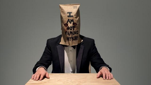 Shia LaBeouf sitzt an einem Tisch mit einem Anzug. Er trägt wieder einen Kartonhut.