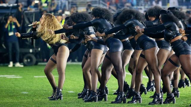 Beyoncé singt auf einem Rasen. Hinter ihr zahlreiche Frauen in schwarzem, knappen Lederkostüm.
