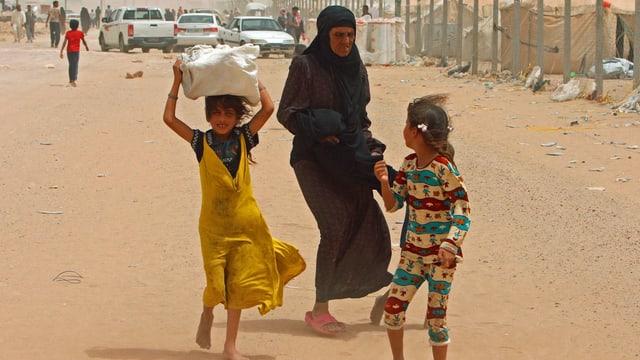Frau mit Kindern auf der Flucht.