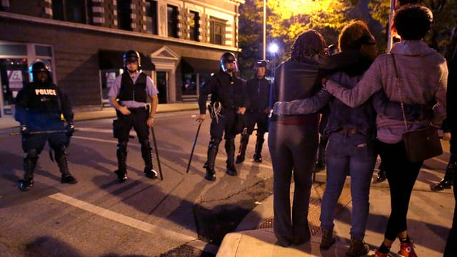 Protestanten Arm in Arm, dahinter Polizisten.