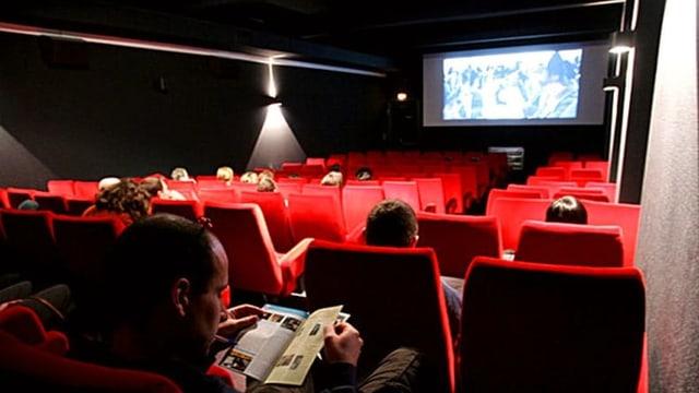 Sala da kino cun intginas persunas che sesan