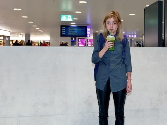 Eine junge Frau mit betrübtem Blick in einer Bahnhofshalle. Sie trinkt einen grünen Saft aus einem Becher.