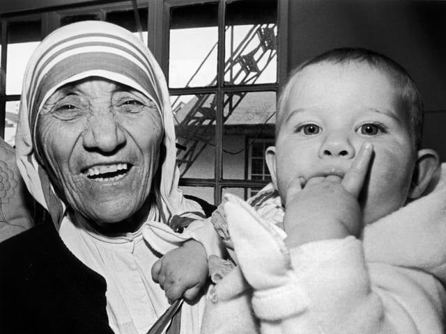 Mutter Teresa hält ein neunmonatiges Schweizer Mädchen während einer Segnungszeremonie.