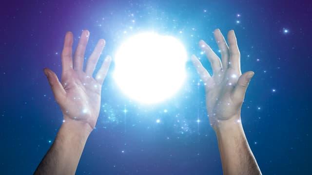 Zwei Hände in der Höh. Sie erzeugen eine Art Leuchtkugel.