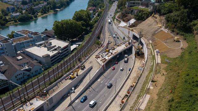 Man blickt von oben auf eine Strasse, auf der Autos fahren. Und ein Tunnel verschwindet rechts in einem Hügel.