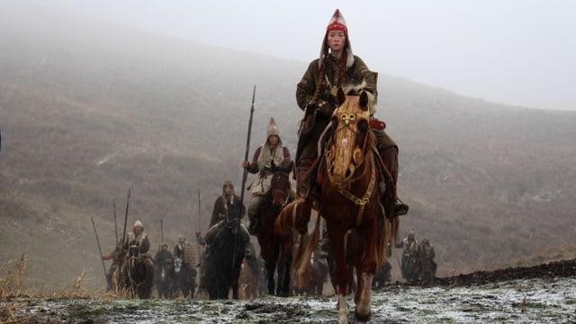 Eine Gruppe von Reitern, angeführt von einer Frau.
