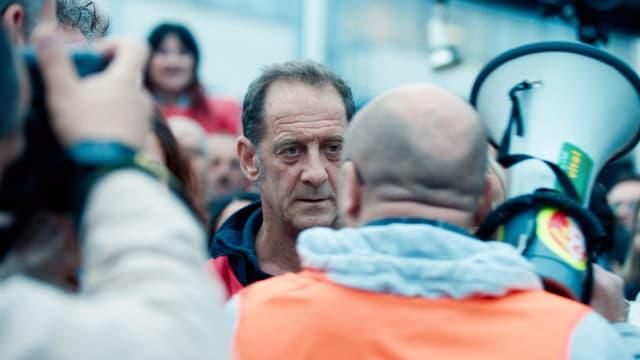 Konfrontation an einer Demo: Ein Mann steht vor einem anderen Mann, sie schauen sich in die Augen.