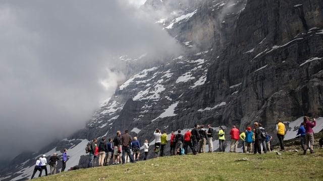 Touristen stehen am Fusse der Eigernordwand.