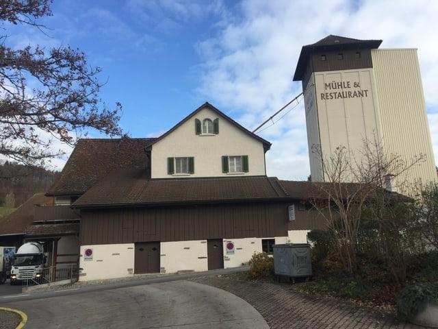 Ansicht der Mühle vn der Strasse aus. Am Betonturm steht «Mühle Restaurant».