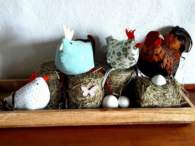selbst gebastelte Hühner sitzen in Holzschhale.