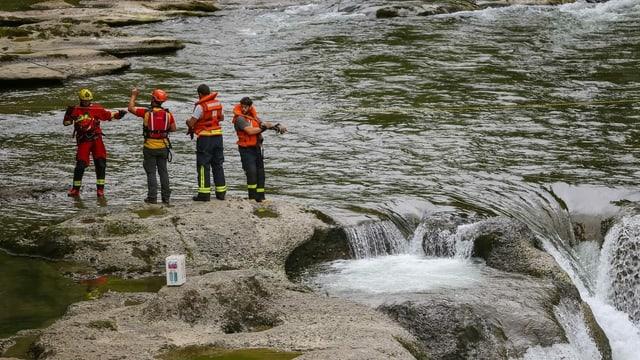 Vier Männer bei Rettungsarbeiten bei einem Wasserfall.