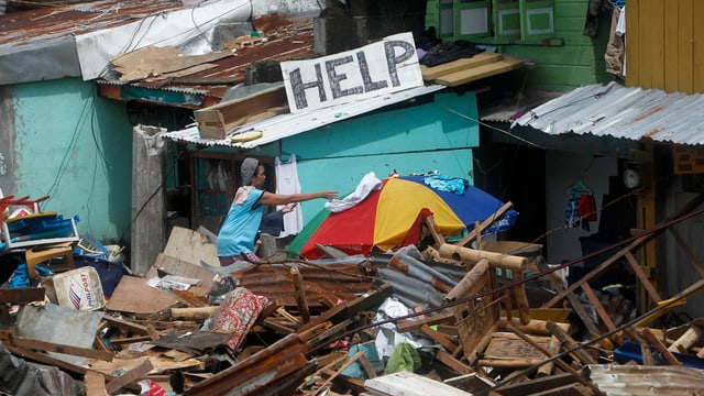 """Ein Mann in Trümmern vor einem Schild mit der Aufschrift """"helft uns""""."""