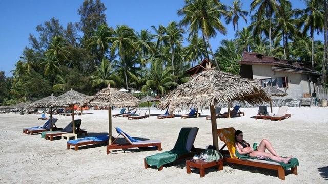Eine Touristin liegt an einem von Palmen gesäumten Strand in Burma.