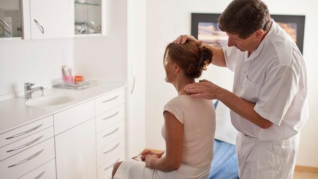Hausarzt untersucht Patientin.