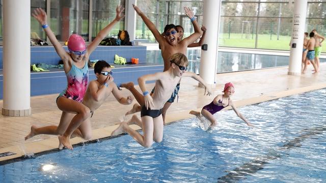 Kinder springen in ein Becken