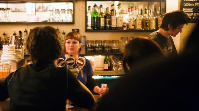 Leute sitzen an einer Bar, eine Kellnerin zapft ein Bier.