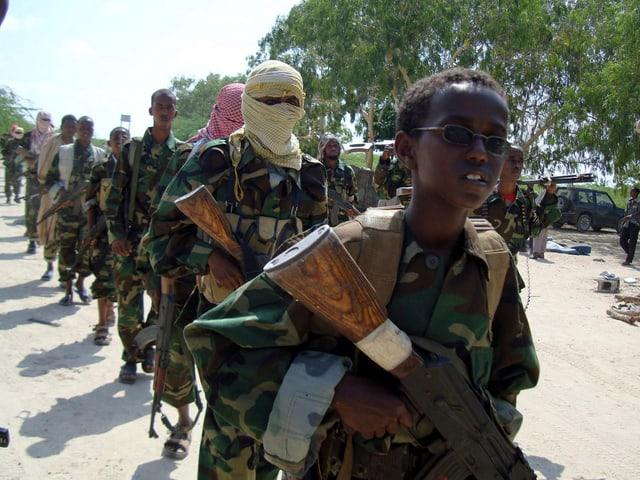Mehrere bewaffnete Soldaten, an der Spitze ein ein junger Knabe mit einer Waffe.