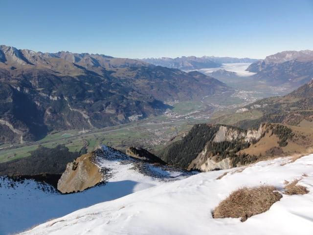 Auf dem Berggipfel liegt zum Teil noch Schnee. Unten im Tal schlängelt sich der Rhein talabwärts und taucht im St. Gallerrheintal in den Hochnebel ein. Darüber ein wolkenloser Himmel.