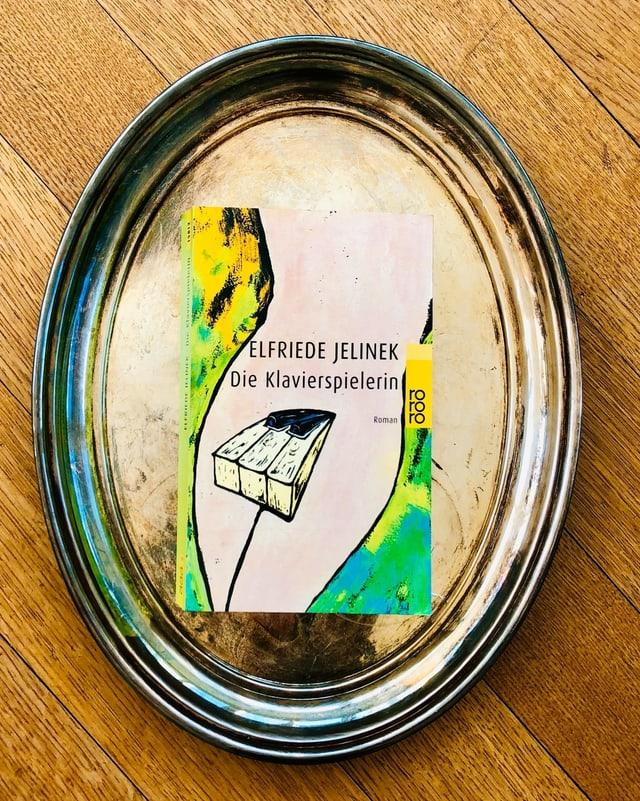 Der Roman «Die Klavierspielerin» von Elfriede Jelinek liegt auf einem Silbertablett