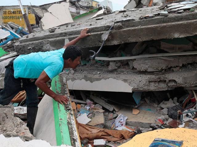 Ein Mann sucht unter Trümmern nach Verschütteten