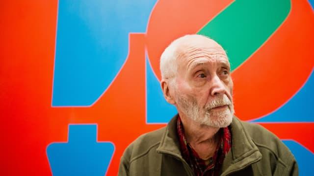 Ein älterer Mann mit Bart steht vor einer Leinwand mit den vier Buchstaben LOVE.