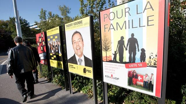 Französische Wahlplakate an einer Strasse, ein Mann geht vorbei.