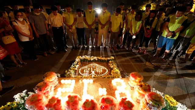 Abitants da Tianjin uran per las unfrendas dals 12 d'avust davant flurs e chandailas.