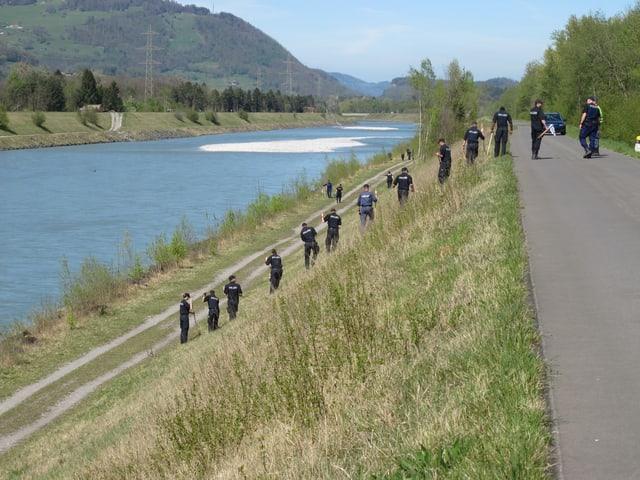 Polizisten durchkämmen denn Rheindamm.