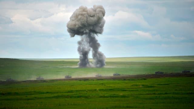 Panzerreihe; dahinter eine Explosionswolke