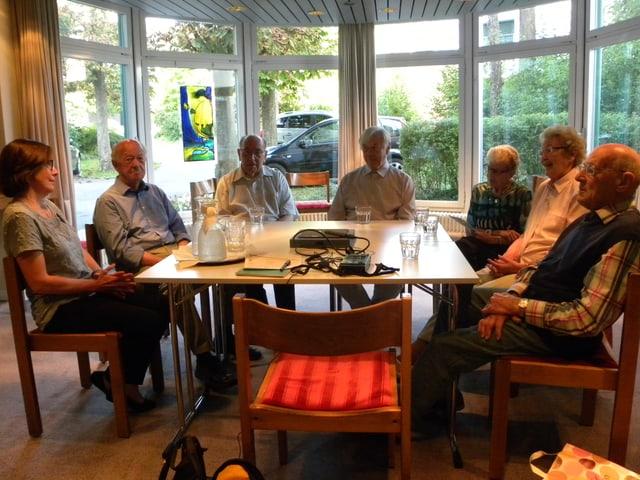 Eine Gruppe von älteren Menschen sitzt rund um einen Tisch.