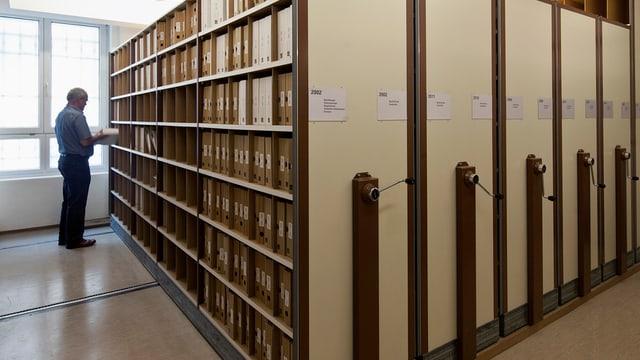 Akten in Archivraum, ein Mann studiert Akten.