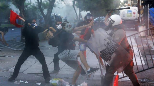 Demonstraten schlagen auf eine Polizistin ein.