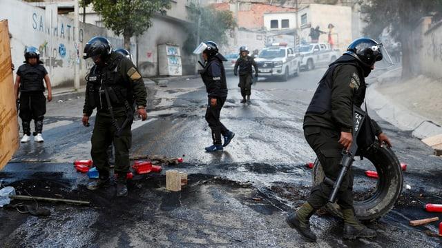 Polizisten in Kampfmontur räumen abgebrannte Barrikaden weg.