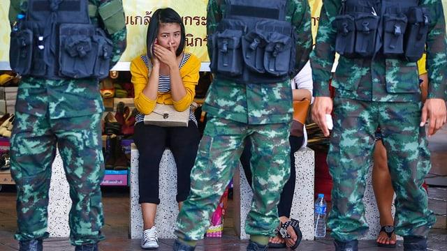 Frau sitzt hinter Soldaten.