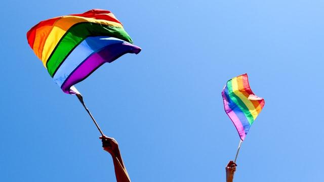Zwei Hände schwingen Regenbogenfahne.